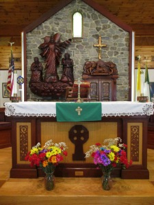 This is the altar at the Shrine Of Our Lady of Knock in East Durham, New York. Behind the altar is a depiction of Our Blessed Mother with St. Joseph and St. John at her sides, with the lamb on the altar to her left.